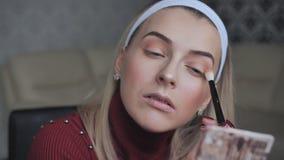 Een blondemeisje past make-up op haar oogleden toe stock video