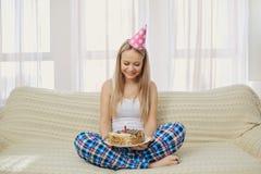 Een blondemeisje in een pyjama GLB met een cake met een kaars celebrat stock foto's