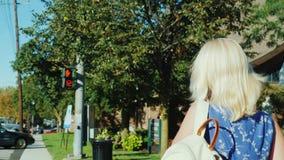 Een blondevrouw met een rugzak kruist de weg Aftelprocedure bij het verkeerslicht Snel ritme van het leven stock video