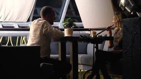 Een blondevrouw rookt een fruitwaterpijp op een datum met een man in een wit overhemd, langzame motie stock videobeelden
