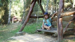 Een blootvoets onbezorgd meisje onderzoekt de camera terwijl het zitten op een brede houten schommeling stock footage