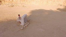 Een blootvoetse mens in witte kleren speelt de piano onder de gele bergen Een vlinder vliegt boven hem Luchtmening stock footage