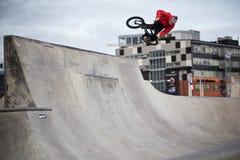 Een bmxruiter in een concrete skatepark met een sprong in de lucht en een rood jasje stock foto