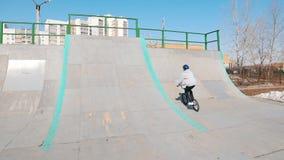 Een bmxruiters die hun vaardigheden in skatepark opleiden Omhoog rennend, uitvoerend een tik en dalend stock videobeelden