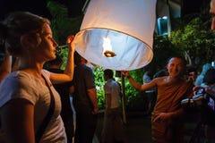 Een Boeddhistische monnik en een toerist geven een drijvende lantaarn in Chia vrij Royalty-vrije Stock Foto