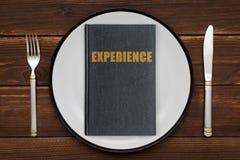 Een boek met de inschrijvingservaring op een plaat Het concept het opdoen van Ervaring stock fotografie