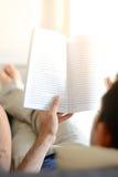 Een boek van de mensenlezing terwijl het liggen op de laag Stock Afbeelding