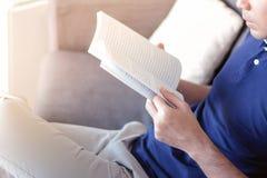 Een boek van de mensenlezing terwijl het zitten op de laag Royalty-vrije Stock Foto