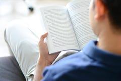 Een boek van de mensenlezing terwijl het zitten op de laag Stock Fotografie