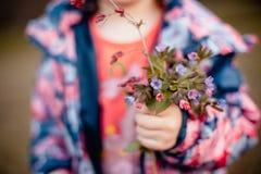 Een boeket van bloemen in de handen van een klein meisje stock afbeelding