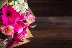 Een boeket van bloemen van lelie, gerbera, witte rozen en alstroemeria op een bruine houten lijst Een vakantie, een gift Stock Afbeelding