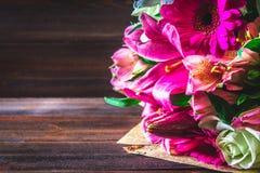Een boeket van bloemen van lelie, gerbera, witte rozen en alstroemeria op een bruine houten lijst Een vakantie, een gift Stock Fotografie