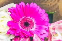Een boeket van bloemen van een lelie, een gerbera, witte rozen en een alstroemeria op een witte houten lijst Een vakantie, een gi Stock Afbeelding