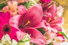 Een boeket van bloemen van een lelie, een gerbera, witte rozen en een alstroemeria op een witte houten lijst Een vakantie, een gi Stock Fotografie