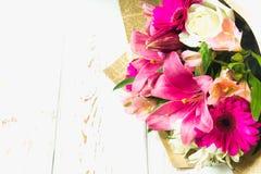 Een boeket van bloemen van een lelie, een gerbera, witte rozen en een alstroemeria op een witte houten lijst Een vakantie, een gi Royalty-vrije Stock Foto