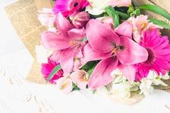 Een boeket van bloemen van een lelie, een gerbera, witte rozen en een alstroemeria op een witte houten lijst Een vakantie, een gi Stock Afbeeldingen