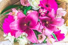 Een boeket van bloemen van een lelie, een gerbera, witte rozen en een alstroemeria op een witte houten lijst Een vakantie, een gi Royalty-vrije Stock Fotografie