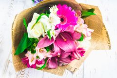 Een boeket van bloemen van een lelie, een gerbera, witte rozen en een alstroemeria op een witte houten lijst Een vakantie, een gi Royalty-vrije Stock Foto's