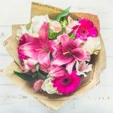 Een boeket van bloemen van een lelie, een gerbera, witte rozen en een alstroemeria op een witte houten lijst Een vakantie, een gi Stock Foto