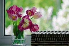 Een boeket van bloemen op een groen lichtachtergrond Magenta tulpen in een vaas Plaats voor uw tekst Mening van het venster stock fotografie