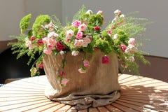 Een boeket van bloemen in potten van jute op een houten tribune op de straat Stock Fotografie