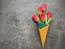 Een boeket van bloemen in een wafelkegel stock afbeelding