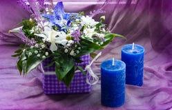 Een boeket van de lente bloeit en blauwe kaarsen op een purpere achtergrond, een concept feestelijke samenstelling, vrije ruimte  Stock Afbeeldingen