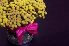 Een boeket van gele tansy in een glasvaas Op vazhe was een lint met een rood lint gebonden Royalty-vrije Stock Foto