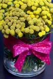 Een boeket van gele tansy in een glasvaas Op vazhe was een lint met een rood lint gebonden Stock Afbeelding