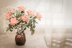 Een boeket van gevoelige rozen bevindt zich in een kleivaas op de lijst stock foto