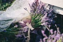 Een boeket van lavendel met een openwork lint wordt gebonden ligt bij het lijstbeen dat stock foto