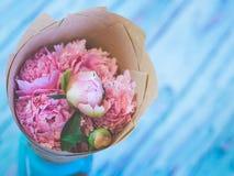 Een boeket van mooie roze pioenen op een blauwachtige houten lijst tegen zacht-geconcentreerde achtergrond Stock Foto