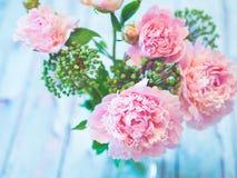 Een boeket van mooie roze pioenen op een blauwachtige houten lijst tegen zacht-geconcentreerde achtergrond Royalty-vrije Stock Afbeeldingen