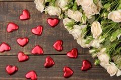 Een boeket van mooie tedere minirozen op een bruine houten lijst met harten Hoogste mening stock foto