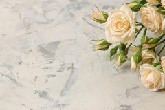 Een boeket van mooie tedere minirozen op een lichte concrete achtergrond Ruimte voor tekst royalty-vrije stock foto