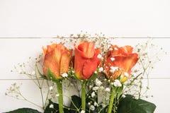 Een boeket van oranje rozen en gypsophila op houten lijst Exemplaar s Royalty-vrije Stock Afbeeldingen