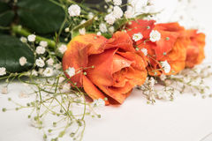 Een boeket van oranje rozen en gypsophila op houten lijst Exemplaar s Stock Foto's