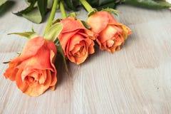 Een boeket van oranje rozen op houten lijst Stock Foto