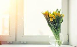 Een boeket van rode tulpen in een vaas op de vensterbank Een gift voor Stock Foto's