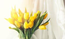 Een boeket van rode tulpen in een vaas op de vensterbank Een gift voor Stock Foto