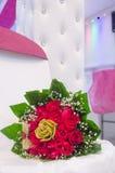 Een boeket van rode verse rozen en een gouden broche met kunstmatige rozen en groene bladeren op een witte stoel Stock Foto's