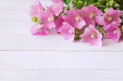 Een boeket van roze wildflowers op een witte houten lijst Stock Afbeelding