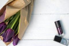 Een boeket van tulpen en purper nagellak: gelukwensen, 8 Maart Internationale Vrouwen` s Dag, 14 de Dag van Februari Valentine `  Stock Afbeeldingen