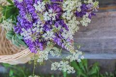 Een boeket van wilde bloemen in een gevlechte mand stock afbeelding