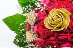 Een boeket van witte rozen en verse gouden broche met kunstmatige rozen en groene bladeren Royalty-vrije Stock Foto's