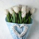Een boeket van witte tulpen in blauw verpakkend document met vrouwenhanden op een witte concrete achtergrond Hoogste mening Vlak  stock foto's