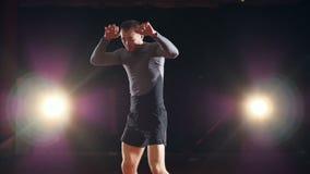 Een bokser pronkt met zijn stempels en schoppen op donkere achtergrond stock videobeelden