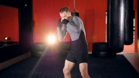 Een bokser treft voor praktijk voorbereidingen door zijn torso uit te rekken stock video
