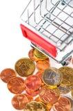 Een boodschappenwagentje met euro muntstukken, symbolische foto voor het kopen van p Stock Afbeelding