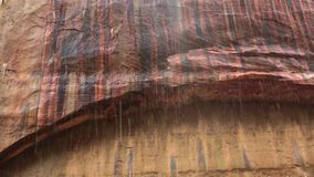 Een boog van zandsteen in het nationale park van Zion heeft stroken van zwarte, rood, koper en gele kleur waar het water neer dru stock video